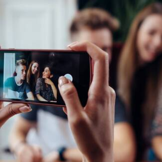 Female hands taking photo with smartphone of young cheerful friends, blurred background.