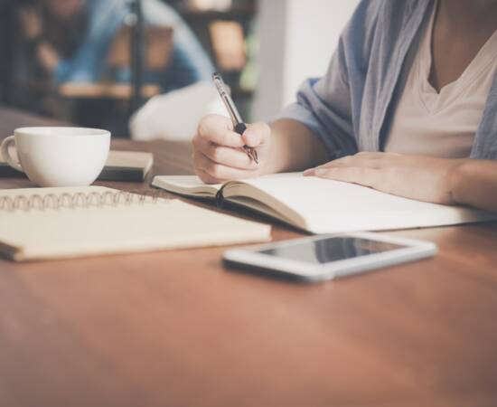 woman-writing-on-a-notebook-beside-teacup-and-tablet-733856 (2)